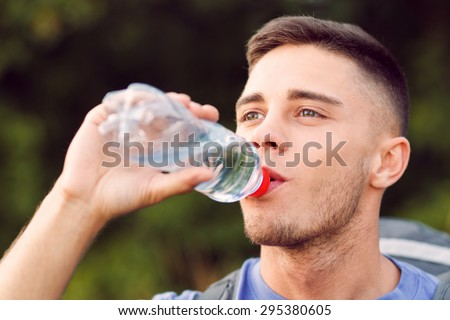 Close up photo of a young handsome tourist wearing blue t-short and backpack standing, drinking water from the bottle