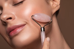 Close up photo of a young woman looking relaxed and smiling while using a natural rose quartz face roller