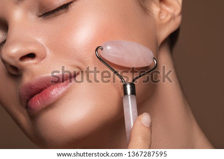 Close up photo of a young woman looking relaxed and smiling while using a natural rose quartz face roller #1367287595