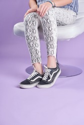 Close up photo of a young woman wearing worn tennis shoes with pattern textured leggings pants on a purple background