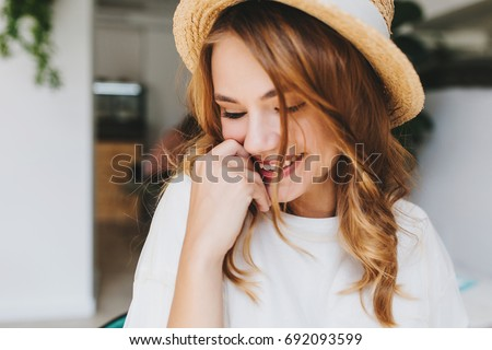 Close-up photo of amazing happy girl with pale skin shy laughing and cover face with hand. Indoor portrait of ecstatic blonde young woman in hat smiling with eyes closed.