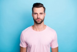 Close up photo of amazing macho guy standing not smiling looking seriously on camera wear casual pink t-shirt isolated over bright blue color background