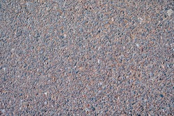 Close up photo of an old cement or asphalt road. Lots of small colorful stones, granite pieces, some concrete mass, sand. Rough and grainy texture.