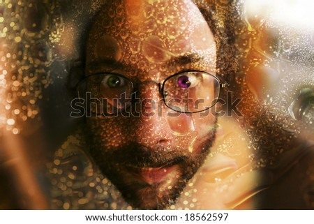 close up photo of bearded man with glasses, purple and green eyes and decorations