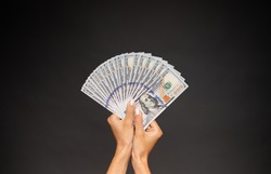 Close up photo of beautiful female hands holding the bunch of dollars of USA isolated on gray background. Economy, business and finance concept