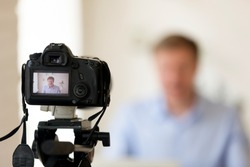 Close up photo of camera on tripod with smiling man image on LCD back screen and blurred scene on background. Male video blogger recording vlog or podcast, streaming online
