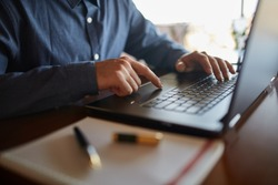 Close-up photo of caucasian male hands typing on laptop keyboard and using touchpad. Notebook and pen on foreground of workspace. Business man working on computer. Isolated no face view.