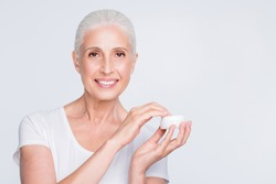 Close up photo of charming lady holding jar with nourishing gel want to apply wearing white trendy stylish t-shirt isolated over white background