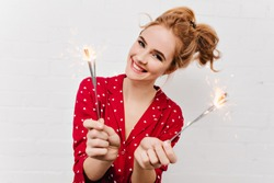 Close-up photo of cheerful caucasian girl holding bengal lights. Portrait of happy young woman in red sleepwear isolated on white background with sparklers.
