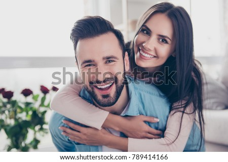 Close up photo of cheerful excited glad careless happy with toothy beaming smile brunette attractive woman and with stylish hairdo man, she is hugging him from the back #789414166