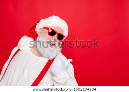 Close up photo of cheerful funny fat overweight style stylish trendy santa claus in eyewear  pointing at copyspace recommend winter season sales isolated over red background