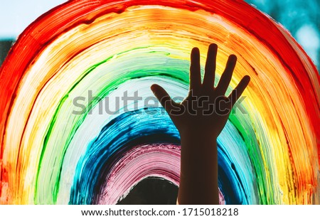 Close-up photo of child's hands touch painting rainbow on window. Family life background. Image of kids leisure at home, childcare, safety joy symbol. ストックフォト ©