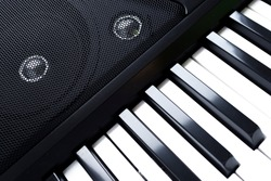 Close up photo of classic electronic digital musical midi piano keyboard or two octaves modern synthesizer and speakers. Music instrument, player concept. Black and white key. Home record music studio