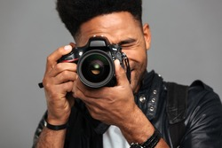 Close-up photo of concentrated afro american man taking photo on digital camera, isolated on gray background