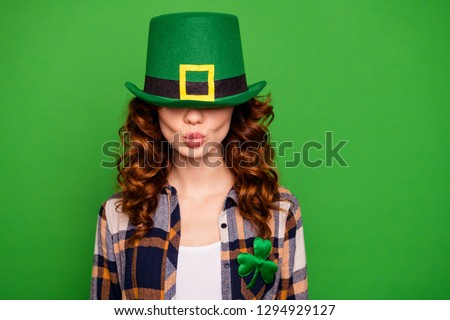 Close up photo of cool pretty she her lady  cap hiding eyes sending air kiss crazy ducky lips shape wearing casual checkered plaid shirt leprechaun headwear isolated on green vivid vibrant background