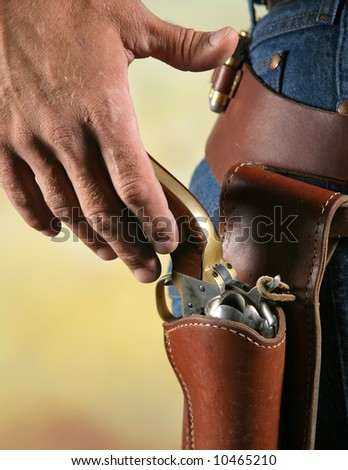 close-up photo of cowboy ready to draw a gun from a holster