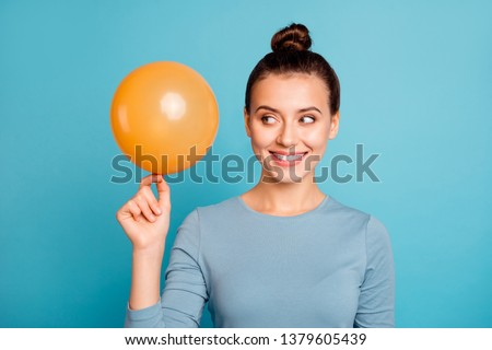 Close up photo of cunning curious lady hold hand orange ballon have idea plan think interested surprise free time dressed cotton modern stylish clothing isolated on blue background enjoy content glad