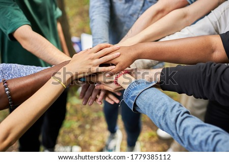 close-up photo of diverse people's hands gathered together, african american and caucasian people as one union. various ethnicities are friends all over the world