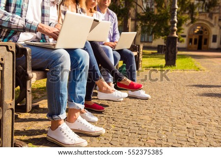 close-up photo of  diverse students sitting on bench and study up with device