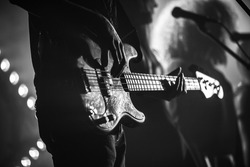 Close-up photo of electric bass guitar player, soft selective focus, live music theme, black and white