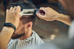 Close-up photo of electric hair clipper and a hair comb in hands of a skillful barber