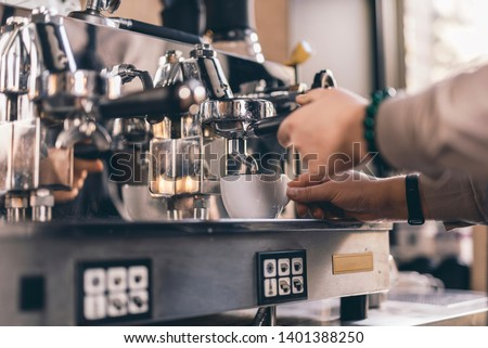 Close up photo of experienced barista touching a cup and a filter holder while pouring coffee from espresso machine