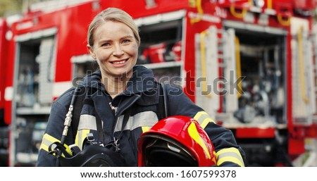 Close up photo of Female firefighter in protective suit with oxygen mask and helmet in her hands