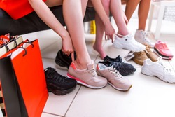 Close-up photo of female legs choosing sports footwear trying on different sneakers in a shopping mall