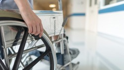 Close up photo of female on wheel chair with orthopedic walking cast. Selective focus at hand with shallow DOF and blurred background with copy space. The wheelchair for disability person.