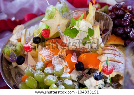 Close-up photo of festive dish with fruit, cheese and sauce