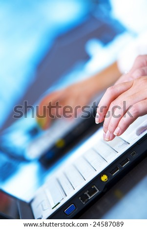 Close up photo of  fingers on keyboard in business environment