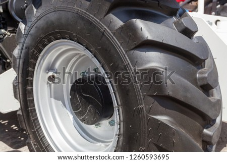 Close up photo of fragment huge tire wheel of construction or agriculture automobile equipment #1260593695