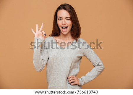 Close-up photo of funny young brunette woman in gray blouse showing OK gesture, looking at camera, isolated on beige background