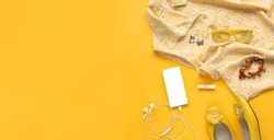 Close up photo of girl lifestyle accessories. Still life of random objects of a modern woman. Floral blouse, earphones, phone, earrings, sunglasses, shoes, top view. Sunny yellow summer colors. banner