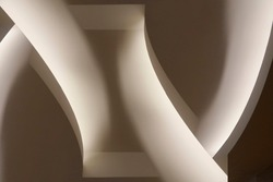 Close-up photo of glowing ceiling structure. Abstract architecture fragment. Modern interior design with curved elements. Geometric composition of curves and surfaces in gray halftones.