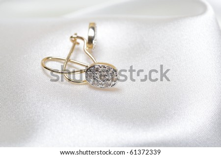 Close up photo of golden ear rings on white textile background