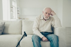Close up photo of grey haired he his him grandparent with walking stick head lean on hand unwell sad wearing casual checkered shirt jeans denim outfit sitting on cozy divan