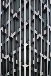 Close-up photo of high-rise building. Lath structure of skyscraper exterior. Modular construction. Abstract modern architecture background in minimal style. Geometric background with polygonal pattern