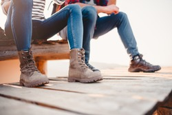 Close up photo of hikers boots on a wooden deck while they resting