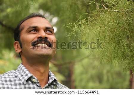 Close-up photo of hopeful, relaxed & happy asian/indian man looking confidently ahead. The executive is wearing a formal shirt & the picture is shot in natural settings