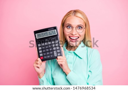 Close up photo of impressed manager holding calculator show statistics scream wow omg wearing mint color shirt isolated over pink background