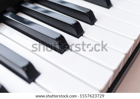 Close up photo of keyboard of piano or electronic digital  midi synthesizer. Side or top view. Musical classic instrument background, music player concept. Black and white classical key. Vintage style