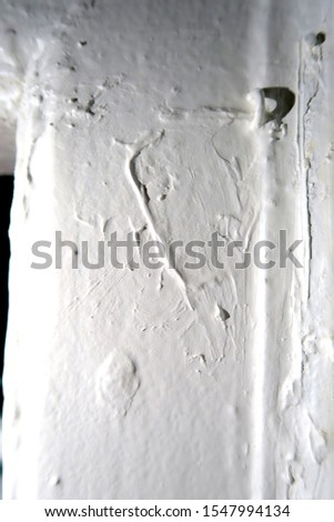 Close up photo of layers of white thick paint with paint blotches and a small metallic loop painted over.