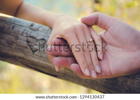 Close-up photo of lovers hands. Boyfriend holding his girl's hand with engagement ring, heart shape carved in the wood in the background