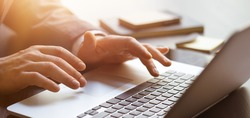 Close-up photo of male hands with laptop. Man is working remotely at home. Distance job