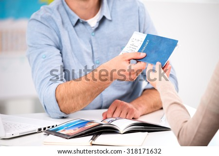 Close up photo of male travel agent and young woman. Young man giving tickets and passport with visa to female tourist