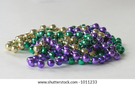 Close up photo of mardi gras beads with room for text