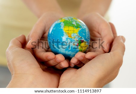 close up photo of mother and child holding hands with a world globe in their hands in better world idea protection and education concept #1114913897