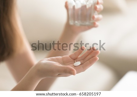 Close up photo of one round white pill in young female hand. Woman takes medicines with glass of water. Daily norm of vitamins, effective drugs, modern pharmacy for body and mental health concept
