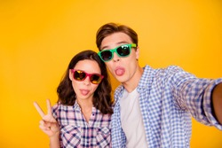 Close up photo of pair in summer specs he him his she her lady boy make take trip weekend common selfies tongue out of mouth wearing casual plaid shirt outfit isolated on yellow background